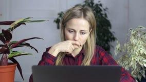 A menina atrativa pensativa senta-se e olha-se na tela do portátil video estoque