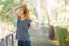 Menina atrativa que aprecia a música nos fones de ouvido que levantam em um fundo do parque Conceito do abrandamento Copie o espa imagens de stock royalty free