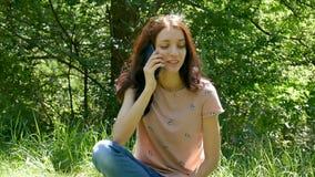 Menina atrativa que chama alguém que usa Smartphone azul no parque Jovem mulher que fala o telefone celular e pelo sorriso video estoque