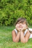 Menina atrativa que encontra-se em um gramado verticalmente Fotografia de Stock