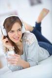 Menina atrativa que escuta a música na cama foto de stock royalty free
