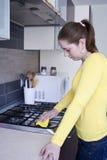 Menina atrativa que limpa um fogão na cozinha Fotografia de Stock