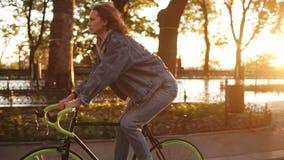 Menina atrativa que monta uma bicicleta no parque ou no bulevar da manhã Opinião lateral uma jovem mulher na montada da roupa oca filme