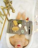Menina atrativa que relaxa no banho com a bandeja de cosméticos Foto de Stock Royalty Free