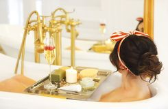 Menina atrativa que relaxa no banho no fundo claro Foto de Stock Royalty Free