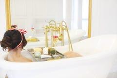 Menina atrativa que relaxa no banho no fundo claro Fotografia de Stock Royalty Free
