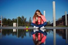 Menina atrativa que senta-se ao lado da água Imagem de Stock