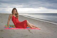 Menina atrativa que senta-se em uma toalha, com vestido vermelho Fotografia de Stock Royalty Free