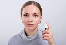 Menina atrativa que toma uma medicina com pulverizador dentro da garganta no fundo claro Fotografia de Stock