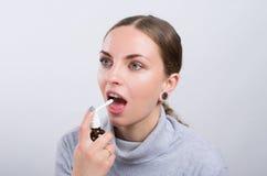 Menina atrativa que toma uma medicina com pulverizador dentro da garganta no fundo claro Fotografia de Stock Royalty Free