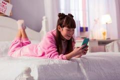 Menina atrativa que usa seu telefone com prazer imagens de stock royalty free