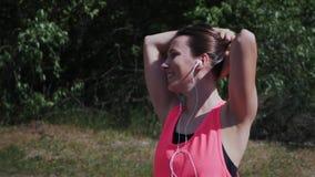 Menina atrativa quente nova nos fones de ouvido que dançam e que cantam a música Música de escuta da mulher desportivo magro no p video estoque