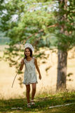 A menina atravessa as madeiras Foto de Stock