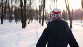 A menina atravessa a câmera do parque do inverno segue-a filme