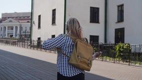 A menina atravessa a cidade e põe sobre sua trouxa traseira cinematic video estoque