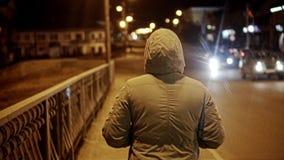 A menina atravessa a cidade na noite Close-up no movimento da parte traseira Luzes da cidade e carros visíveis da passagem vídeos de arquivo