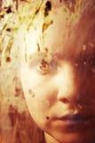 Menina atrás do vidro sujo Fotografia de Stock Royalty Free