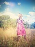 A menina bávara veste um dirndl e guarda um brezel Fotografia de Stock Royalty Free