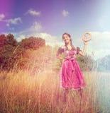A menina bávara veste um dirndl e guarda um brezel Imagens de Stock Royalty Free