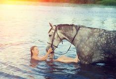 A menina banha o cavalo em um rio Fotos de Stock Royalty Free