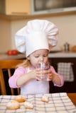 A menina bebe a água na cozinha usando o vidro Imagens de Stock Royalty Free