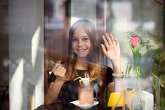 A menina bebe o café e olha o vídeo no telefone celular Fotografia de Stock Royalty Free