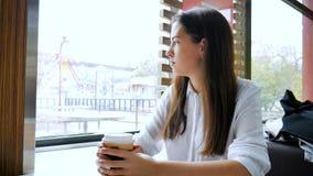 A menina bebe o café em um café video estoque