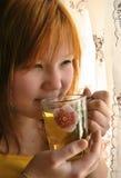 A menina bebe o chá Fotografia de Stock