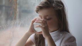 A menina bebe o leite de um vidro video estoque