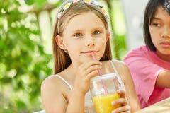 A menina bebe o suco de laranja fresco para o café da manhã foto de stock royalty free