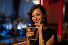 A menina bebe um cocktail no clube noturno Fotos de Stock Royalty Free