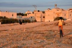 Menina beduína em uma bicicleta perto das casas no deserto do Negev, Israel Fotos de Stock