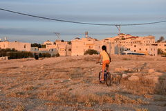 Menina beduína em uma bicicleta perto das casas no deserto do Negev, Israel Foto de Stock