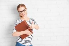 Menina bem sucedida feliz do estudante com o livro que mostra os polegares acima Foto de Stock Royalty Free