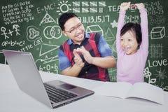 Menina bem sucedida que levanta as mãos na classe Fotos de Stock