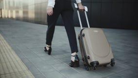 A menina bem sucedida rola uma mala de viagem em roda na área de reivindicação de bagagem filme