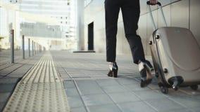 A menina bem sucedida rola uma mala de viagem em roda na área de reivindicação de bagagem vídeos de arquivo