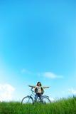 Menina, bicicleta e céu bonitos. Imagens de Stock