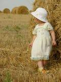 Menina bienal no chapéu perto do feno dos pacotes na do campo foto de stock royalty free