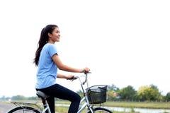A menina biking com céu imagem de stock