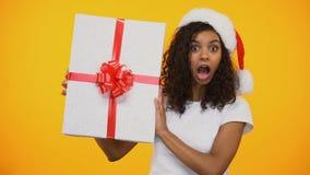 Menina biracial alegre no chapéu de Papai Noel que diz o wow e que mostra o giftbox enorme video estoque