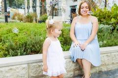 Menina blondy emocional pequena bonito da criança no vestido com a mãe grávida que joga, bolhas de sabão de travamento durante a  fotos de stock