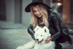 Menina bonita, à moda vestida que abraça na rua um grande cão Imagens de Stock