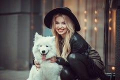 Menina bonita, à moda vestida que abraça na rua um grande cão Fotos de Stock
