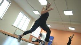 A menina bonita é contratada em um fitness center usando o método moderno do tabata, mo lento filme