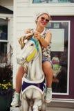 A menina bonita abraça o cavalo do brinquedo Fotografia de Stock