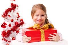 A menina bonita abraça um pacote do presente Fotografia de Stock