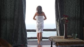 A menina bonita abre cortinas e corridas ao terraço da opinião do mar Mulher 'sexy' nova que acorda os braços dos estiramentos qu filme