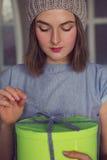 A menina bonita abre uma surpresa da caixa de presente Imagens de Stock