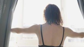 A menina bonita ? acordada e estando antes da janela Cortinas de abertura bonitas da mulher e vista atrav?s da janela vídeos de arquivo